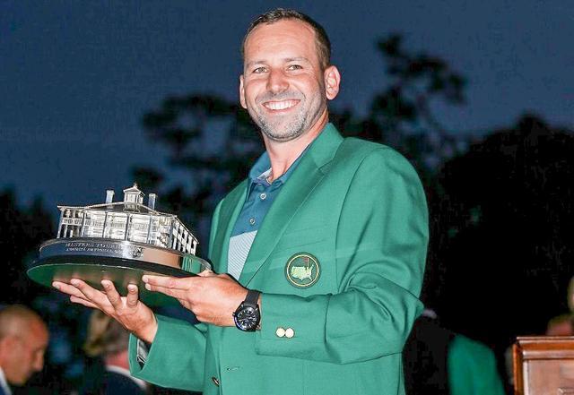 画像: グリーンジャケットに手を通し、満面の笑みを浮かべるガルシア