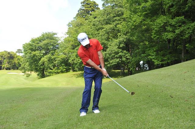 画像: 腰から上を傾斜なりに右に傾け、傾斜なりに振るのがコツ。これくらいの傾斜なら番手はSWでオッケー