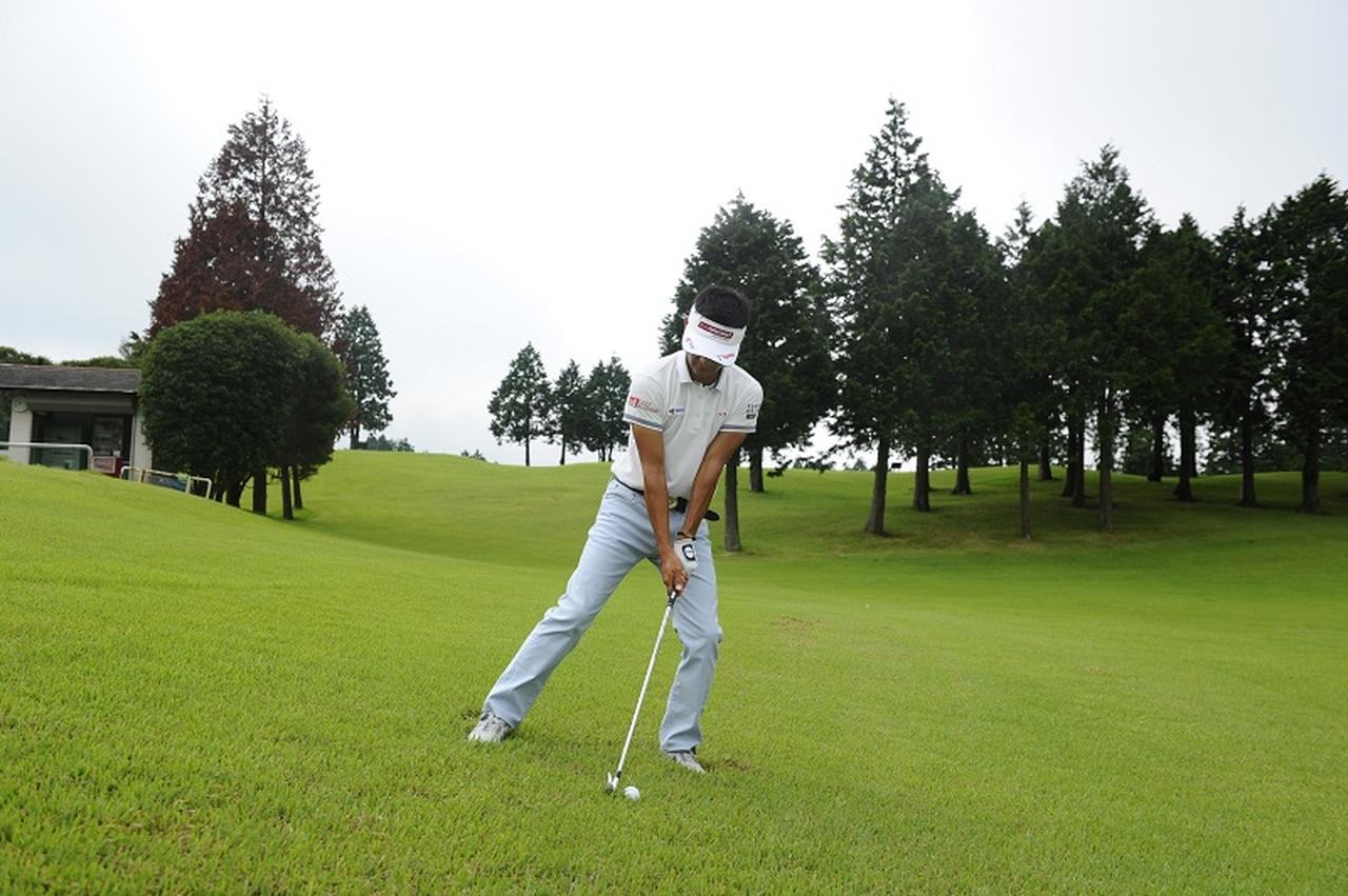画像: なるべく傾斜に逆らわずに傾斜と平行に構えれば、低いほど左足に体重が自然に多く乗る。構えたときのこの左ひざの角度を、スウィング中はキープするようにする