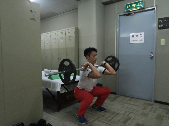 画像: ロッカーでスクワットをする栖原トレーナー(写真提供/吉田洋一郎)