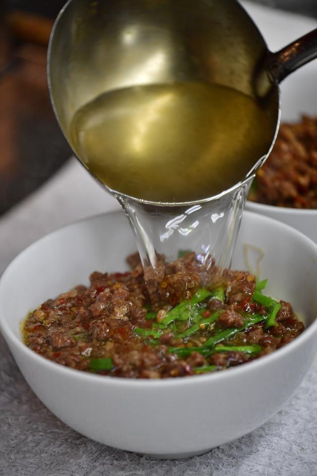 画像: 麺や具材を盛り付けた後に熱々のスープを流し込む