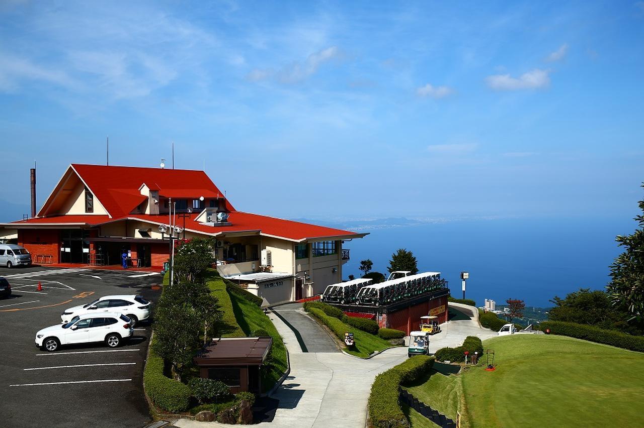 画像: 赤い屋根のクラブハウス。後ろには海が広がっている