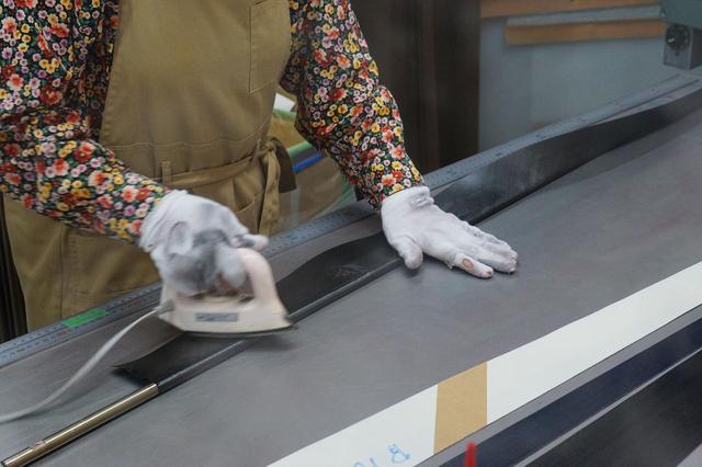 画像: 簡単に巻いているように見えるが、アイロンで熱を加えながら手早く芯棒に巻き付けていく。