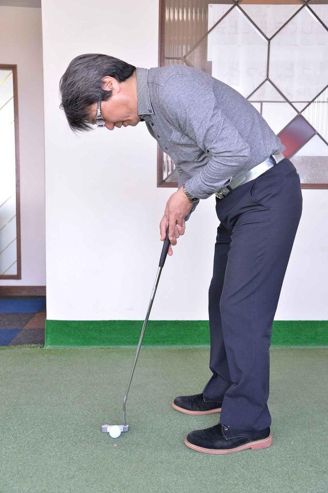 画像: パターをアップライトにして目線の真下にボールが来るぐらい近く立てれば、それだけヘッドはストレートに動きやすい。おのずと背中が丸まり、後頭部が水平になる姿勢になる。ライ角はルールで80度以内に規制されている