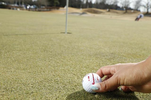 画像: ボールにマジックで線を引いて、その線を打ち出したい方向に1球1球、丁寧に合わせる