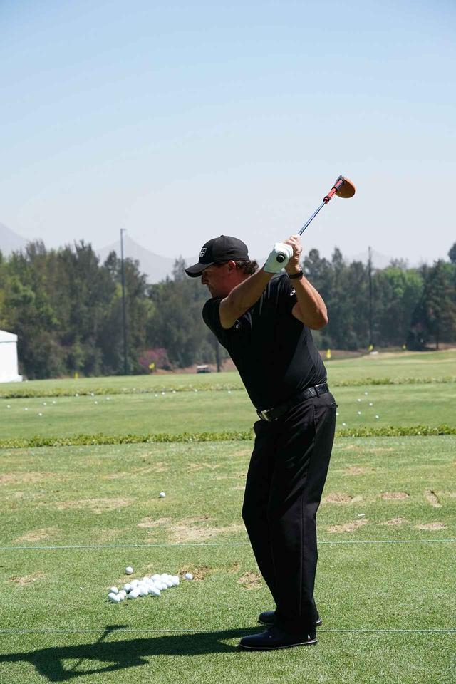 画像: 黄色いヘッドの重いドライバーにさらに重りをつけて素振りをしている