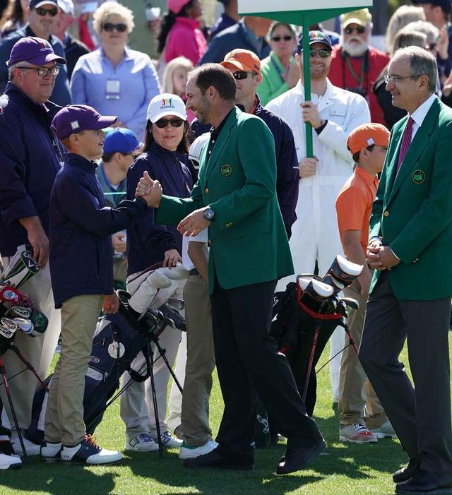 画像: グリーンジャケットを着用し、ジュニア選手と握手する昨年のマスターズ優勝者、セルジオ・ガルシア。