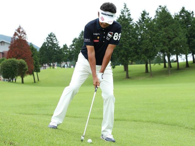 画像: 左足体重で左股関節上に軸を感じながら斜面なりに構える。フェードが出やすいぶん、目標よりも少し左を向いて構える