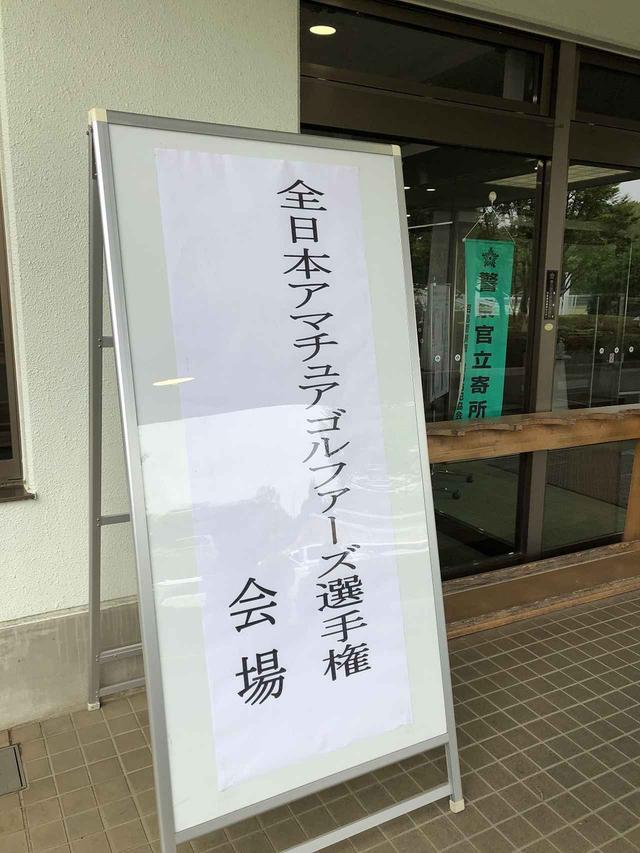 画像: 全日本アマチュアゴルファーズ選手権の看板が設置された会場入り口。次は全国への切符をかけた「地区決勝」が待っている