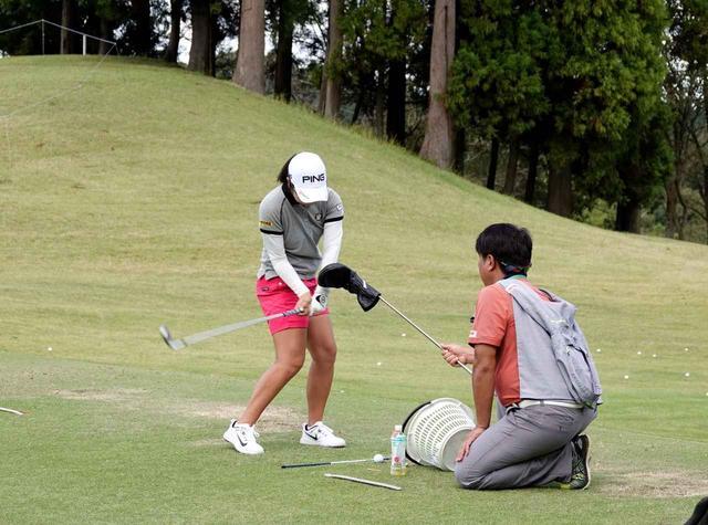 画像: 練習ラウンド後の練習場で辻村コーチと調整する比嘉真美子