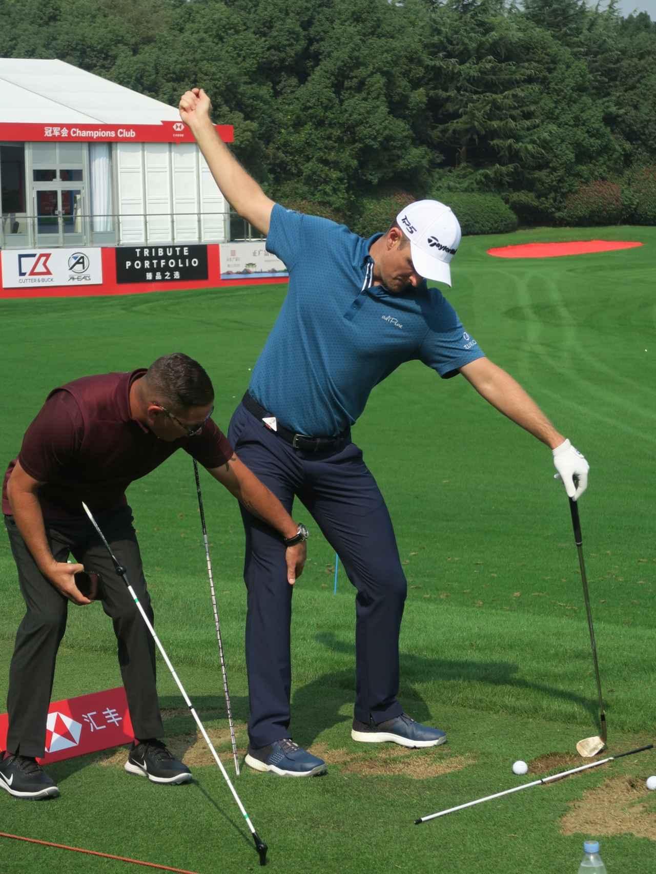 画像: コーチのショーン・フォーリー(写真左)とスティックを3本使い、課題を修正するためのドリルを行うローズ
