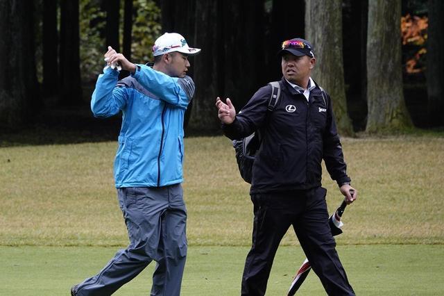 画像: 練習ラウンドを回っているあいだも飯田トレーナーにスウィングの相談をしていた