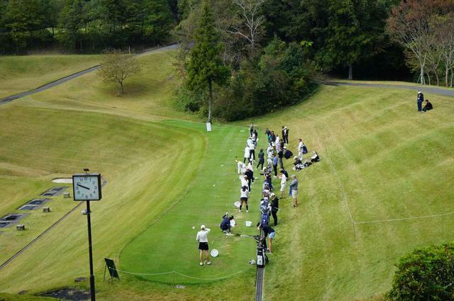 """画像: 練習場でショットの調整をする選手と""""ツアーレップ""""と呼ばれるゴルフ関係者"""