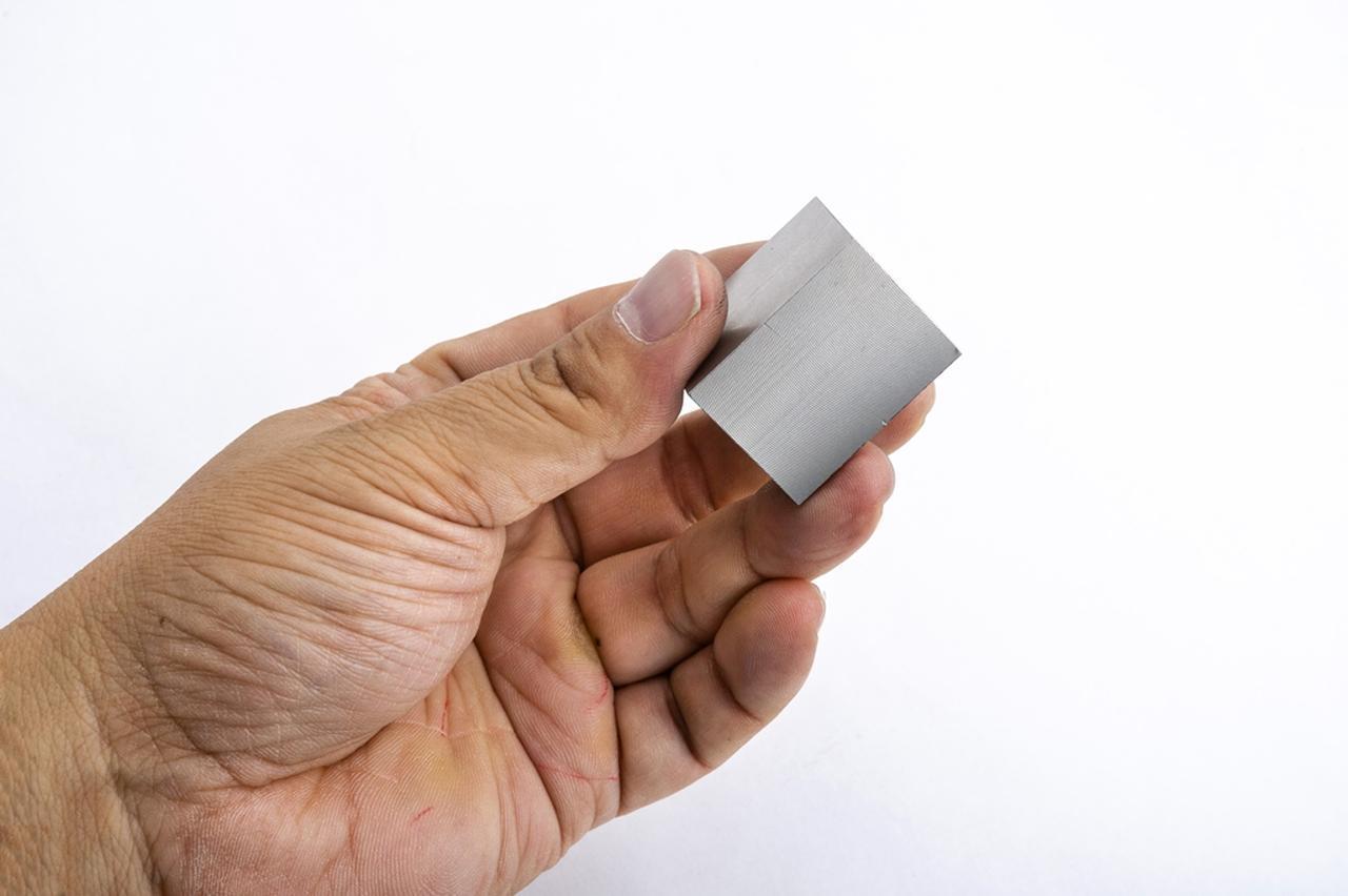画像: (写真1)指先でつまみ上げたステンレスのキューブ。これがドライバーヘッドと同じ重さ