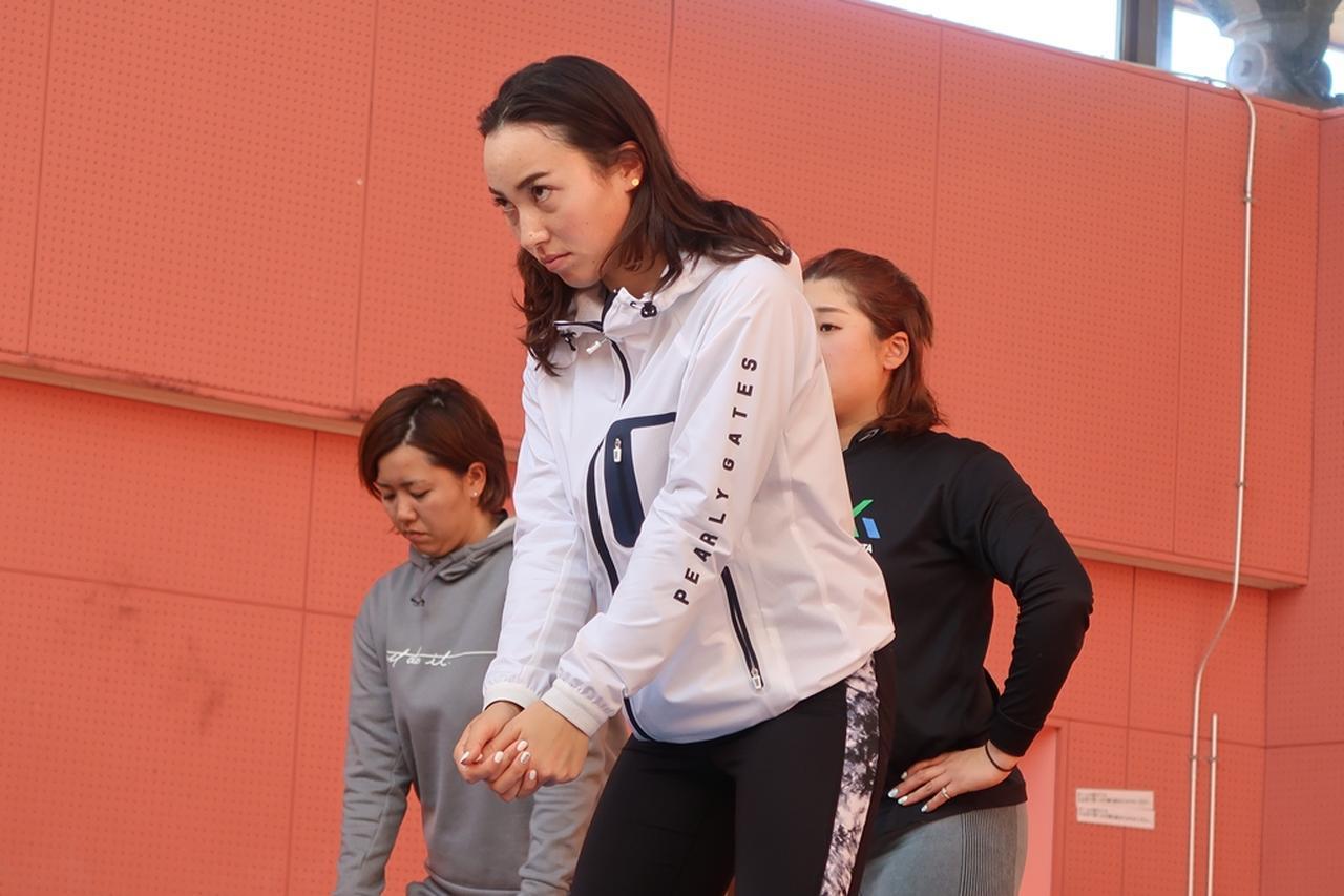 画像: トレーニングの効果を実際のスウィングに落とし込むべく鏡を見ながらアドレスをチェックする村田理沙