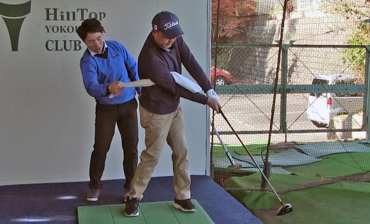 画像: インパクトでは右脇に挟んだタオルを強く締め込む感覚でボールを押し込むイメージを持つのがコツ