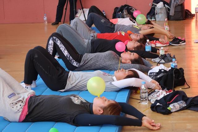 画像: 様々な姿勢で風船をふくらませる女子プロたち