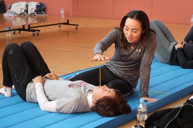 画像: 村田理沙(右)と長田若菜(左)がペアを組み、ストローを使って呼吸法を学ぶ。息を長く吐き続けるトレーニングだ