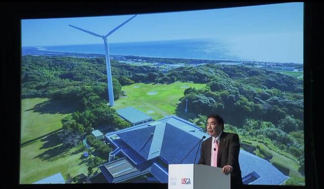 画像: 登壇する藤田氏。背後のモニタには浜名湖CCに屹立する巨大な風車が見える