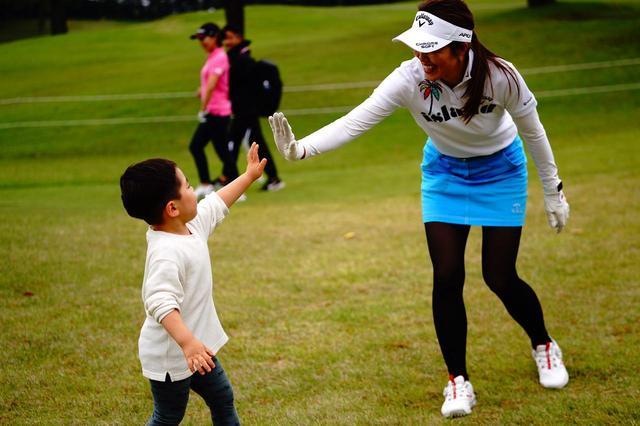 画像: 練習ラウンドを終えてハイタッチ。働く間息子を誰に、あるいはどこに預けるか。女子プロゴルファーでも、会社員ママと悩みは同じ