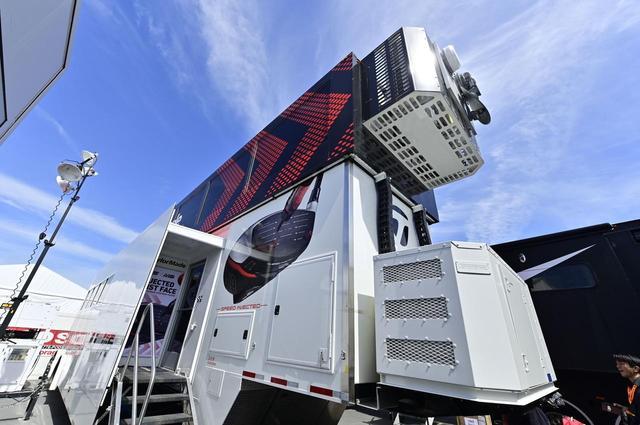 画像: 一際目をひく巨大トラック。なんと2階建てのテーラーメイドのツアーバンと呼ばれるバスだ