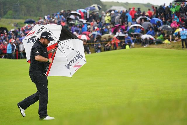 画像: 傘を横に差すほどの強い雨風が選手たちを襲う