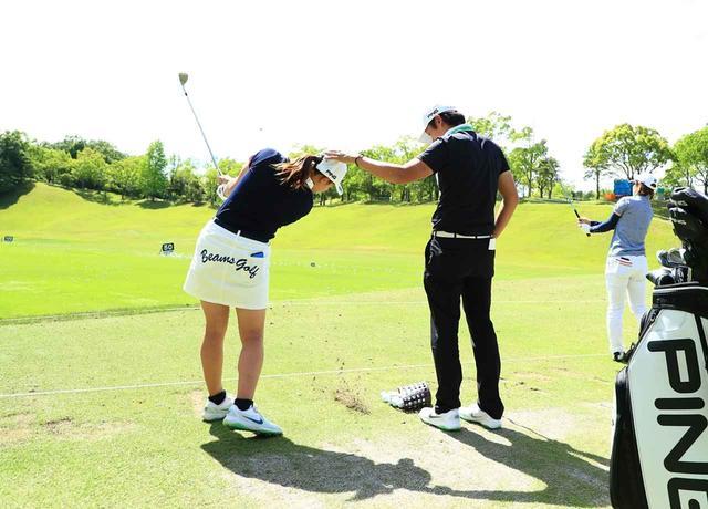 画像: ツアーの練習場でも青木コーチに頭に手をポンと置いてもらいながらスウィングをチェック