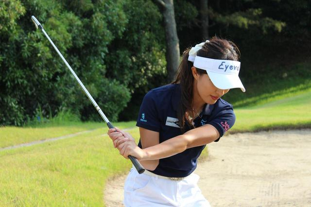 画像: より球を上げるためスウィング中に左手首を甲側に折る小澤。