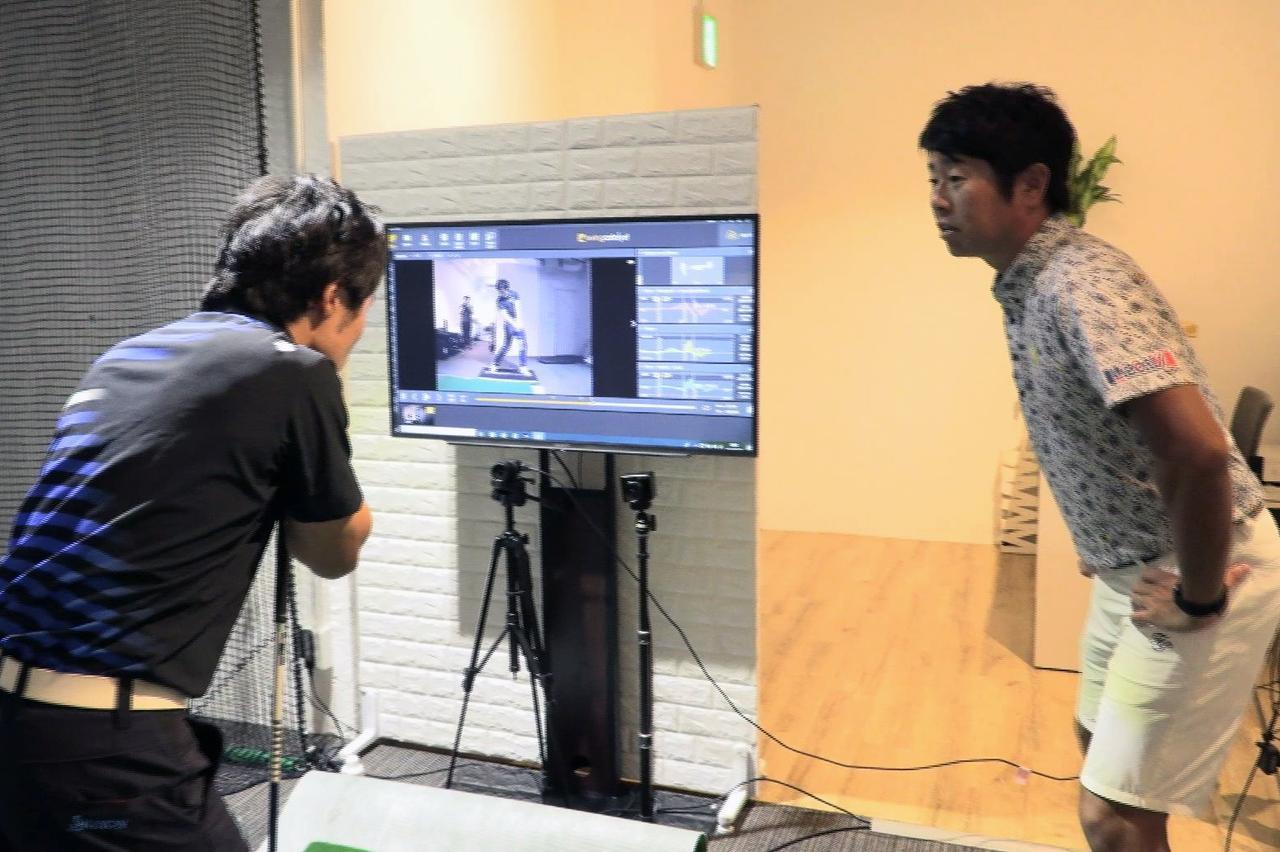 画像: 早速3Dモーションプレート「スウィングカタリスト」を使って原田のスウィングを説明する石井。原田も真剣だ