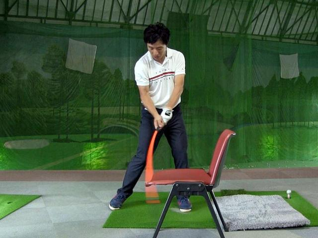 画像: 素振り練習用シャフトと椅子を用いた、しなり戻りの感覚をつかむドリル。しっかりしなりを使えていれば、椅子に引っかかることなく先端部が座面の下に入る