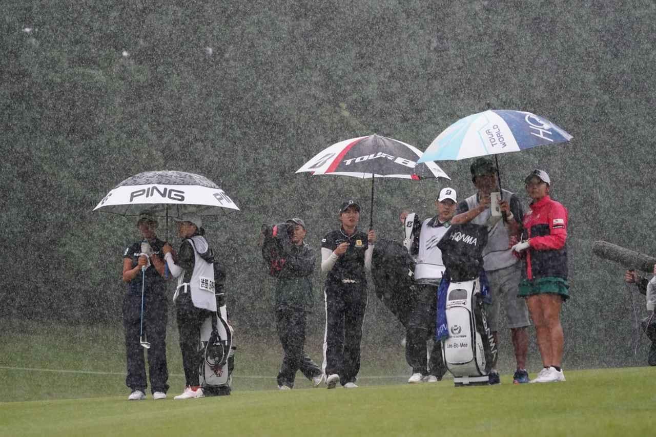 画像: 左から渋野日向子、大里桃子、イ・ボミのペアリング。雨がどしゃ降りになり、15分ほどプレーが中断された(撮影/大澤進二)