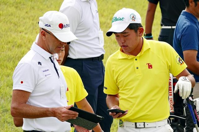 画像: ナショナルチームのヘッドコーチ、ガース・ジョーンズ(左)とタブレットを見ながら話し合う米澤