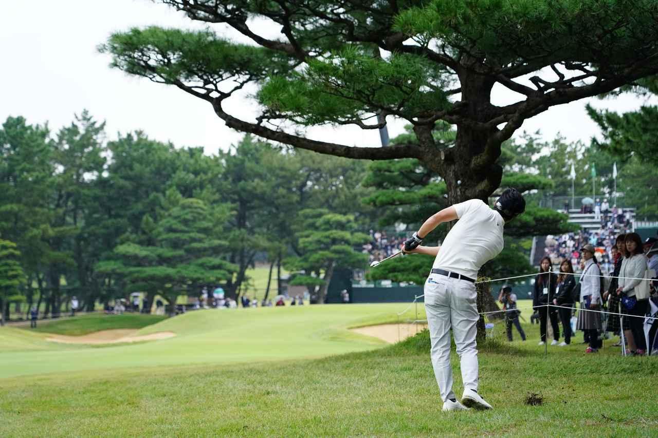 画像: 最終18番パー4で樹の後ろからグリーンを狙う石川遼