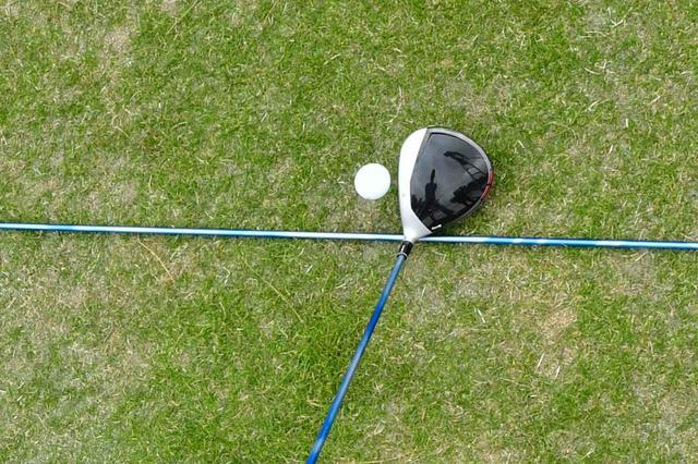 画像: 地面に置かれた青棒で示された仮想のクラブ軌道に対し、フェースが閉じている(左を向いている)場合、ボールは左に曲がる