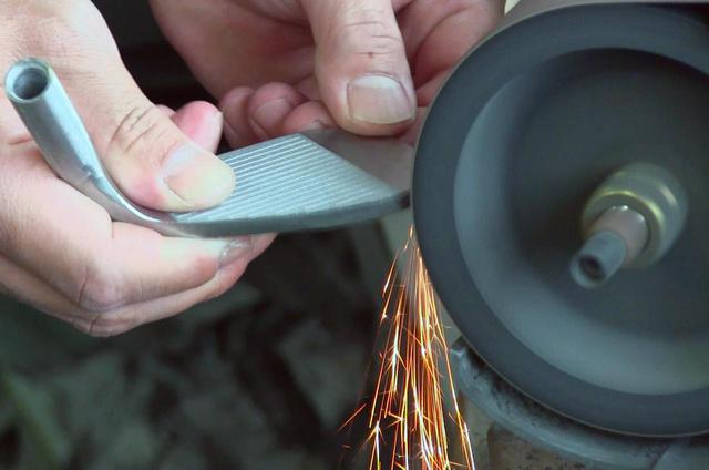 画像: 火花を散らしながら研磨機で少しずつヘッドを削っていく