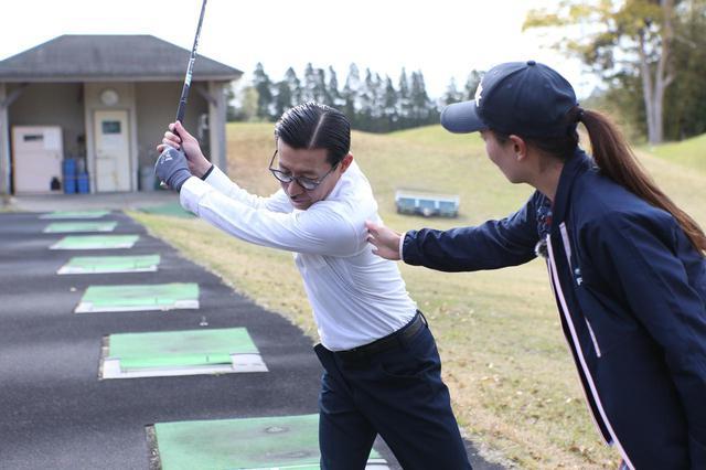 画像: ダウンスウィングで右肩が左に出ないように指導をする高島