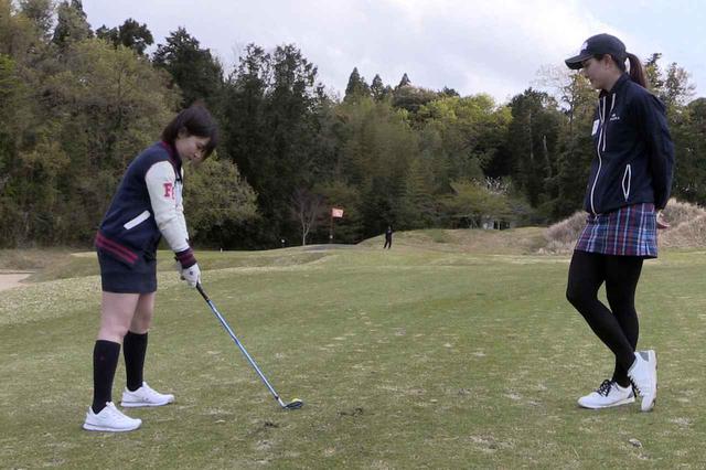 画像: 苦手なハーフショットのアプローチを克服すべく、高島の指導を受ける飯田