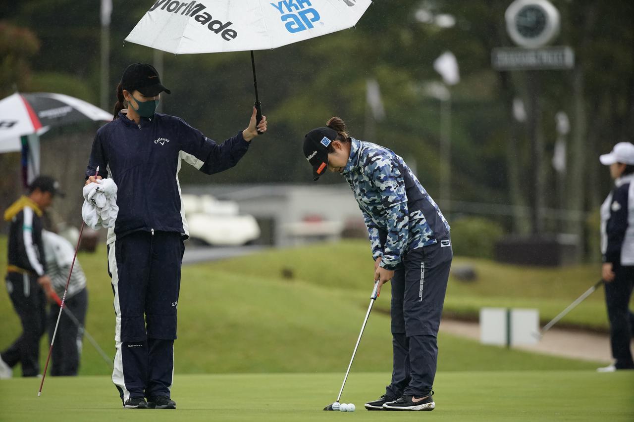 画像: 雨の中、藤田は大西に傘をさしかける(写真は富士通レディース2020 写真/大澤進二)