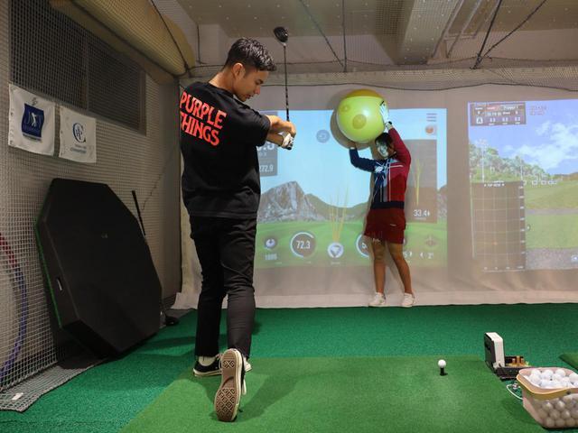 画像: 写真A:高島が持ち上げている黄色いバランスボールにボールを通すイメージでスウィング