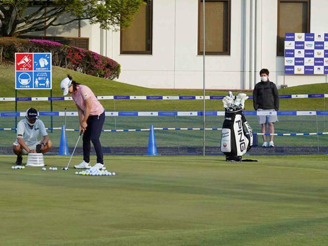 画像: 渋野のパット練習を柵の奥から見守る斎藤トレーナー。現在国内女子ツアーに関しては、トレーナーは有観客試合の場合のみ会場入りができるという(写真は2021年のアクサレディス)