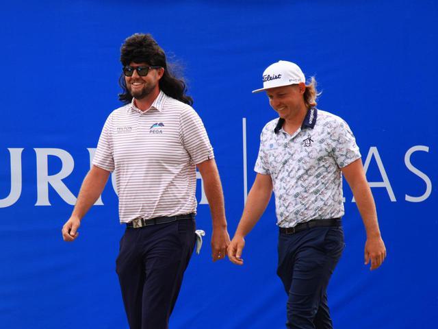 画像: PGAツアー「チューリッヒ・クラシック・オブ・ニューオリンズ」3日目に、キャメロン・スミス(右)の髪型に似せたマレットのかつらを被って登場したマーク・リーシュマン(左)(写真/Getty Images)