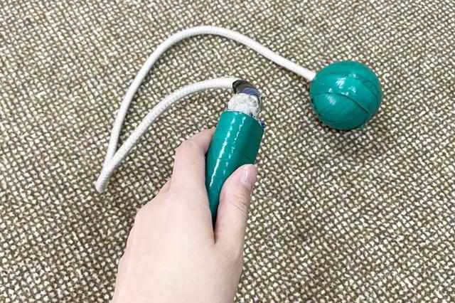 画像: まず最初に紹介するのは「名前はありません(笑)」というけん玉のように持ち手の先にひもがつき、ひもの先端に重りがついている練習器具