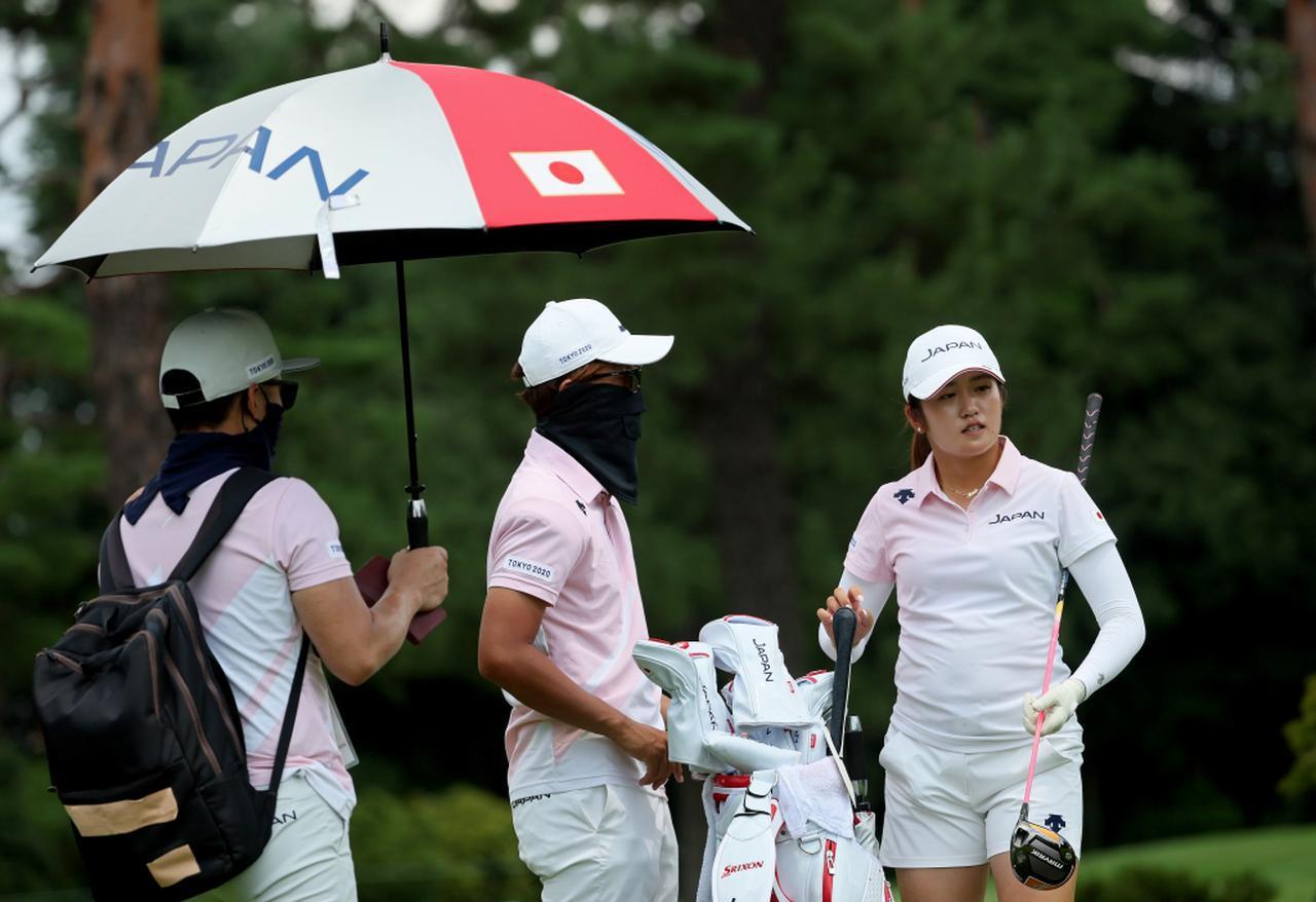 画像: 日本代表としてオリンピック女子ゴルフに出場する稲見萌寧(右)と、そのコーチであり本大会ではキャディとしてバッグを担ぐ奥嶋誠昭(中)(写真/Getty Images)