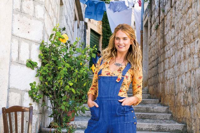 画像: 若きドナ(リリー・ジェームズ) オックスフォード大を卒業し、自分の運命探しの旅に出て、ギリシアのカロカイリ島にたどり着く。その途中で3人の異なる魅力を持った男性たちと出会う。