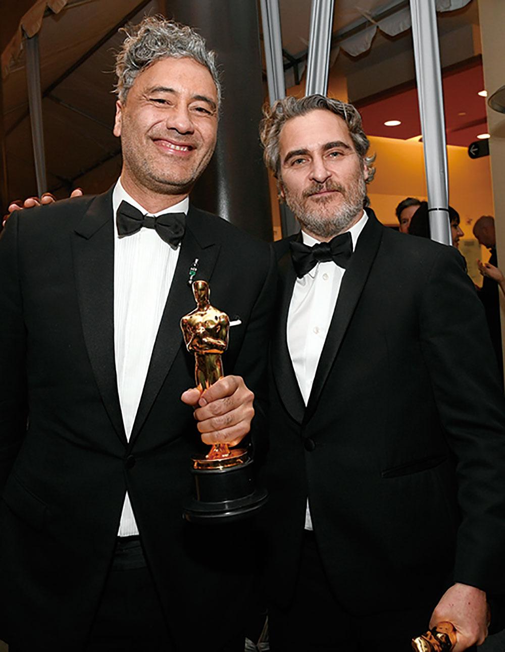 画像: 脚色賞を受賞したタイカ・ワイティティーと主演男優賞のホアキンが互いを讃えあう