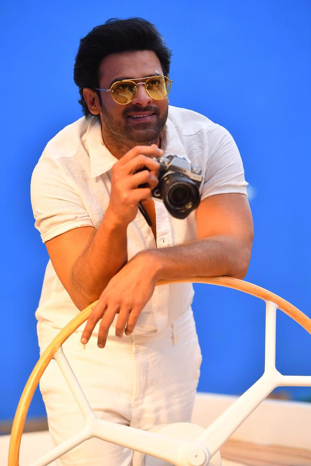 画像: ヨットの上でカメラを手にするプラバース