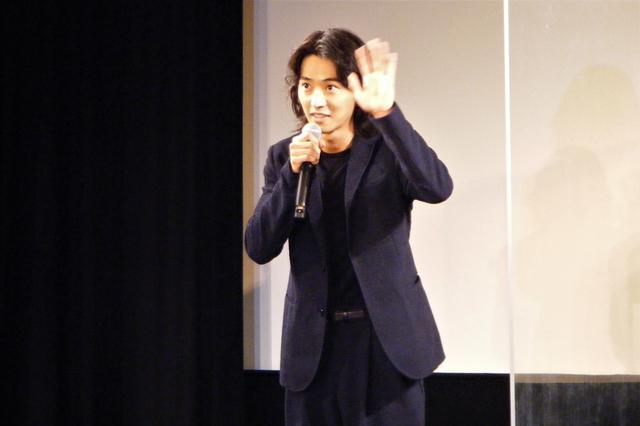 画像: リモート中継でつながっている観客へ手を振る山﨑賢人