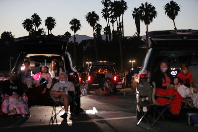 画像: 南カリフォルニアのドライブインで行なわれた催しを楽しみに来た住民たちは一様にマスクをつけている Photos by Getty Images