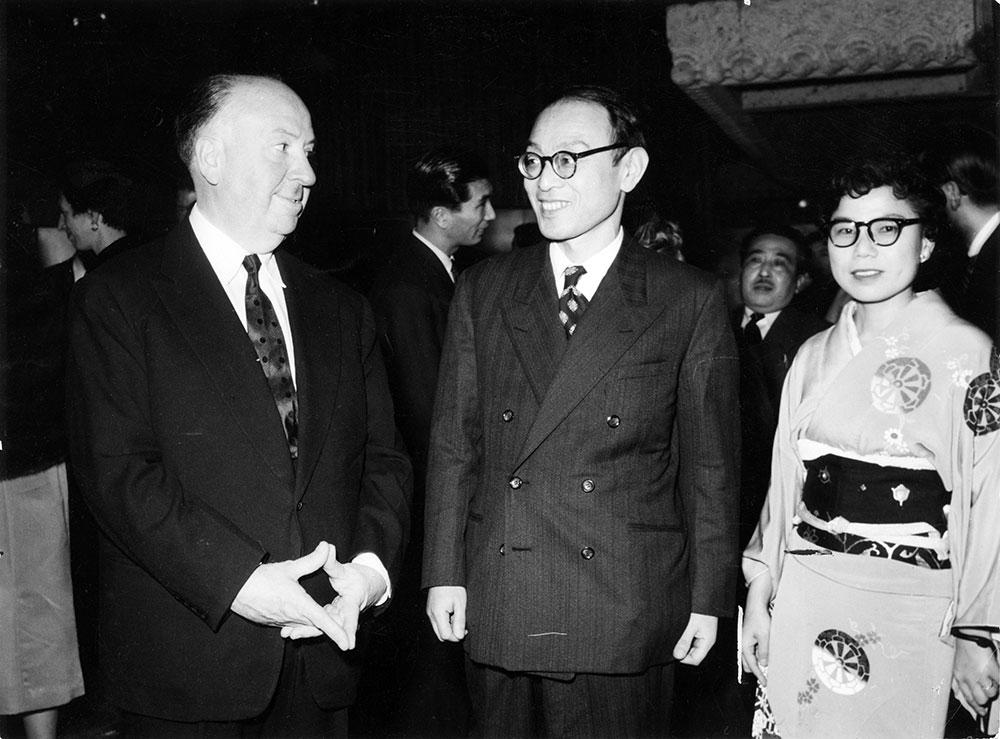 画像: 1955年に初来日したアルフレッド・ヒッチコック監督と談笑する評論家の双葉十三郎さん、本誌・石井編集長(初代)