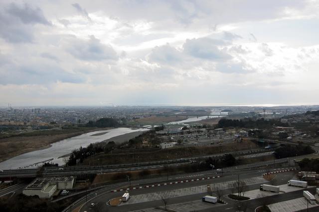画像: 手前が東名高速、左奥が富士市街、右奥に駿河湾が光っている。